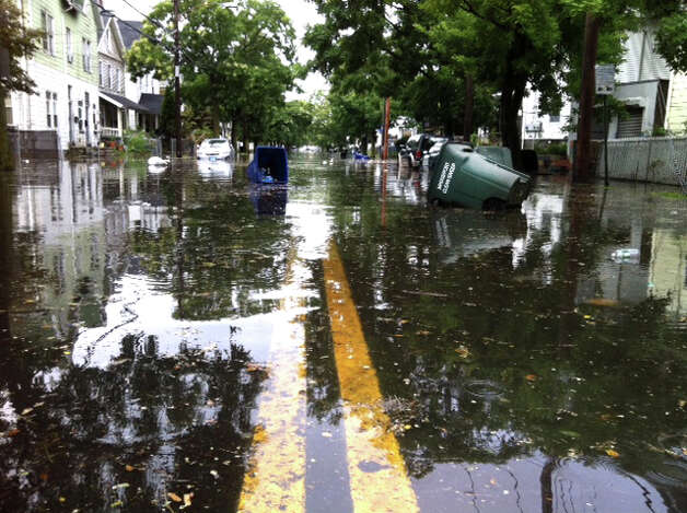 After a heavy rain, trash cans float on a flooded Iranistan Avenue in Bridgeport Conn. on Friday August 10, 2012. Photo: Ned Gerard / Connecticut Post