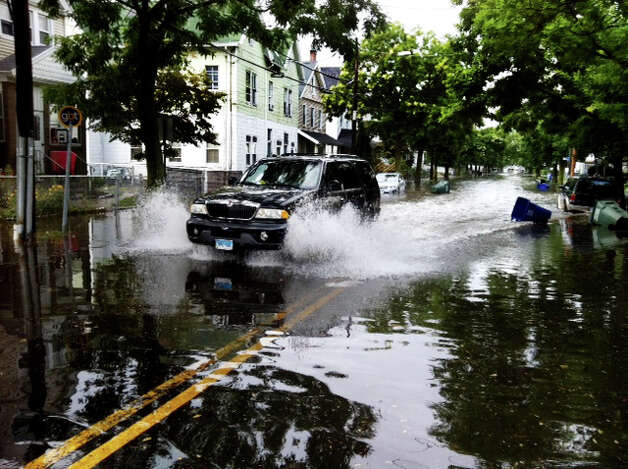 A vehicle drives through a flooded Iranistan Avenue in Bridgeport Conn. after a heavy rain on Friday August 10, 2012.on Friday August 10, 2012. Photo: Ned Gerard / Connecticut Post