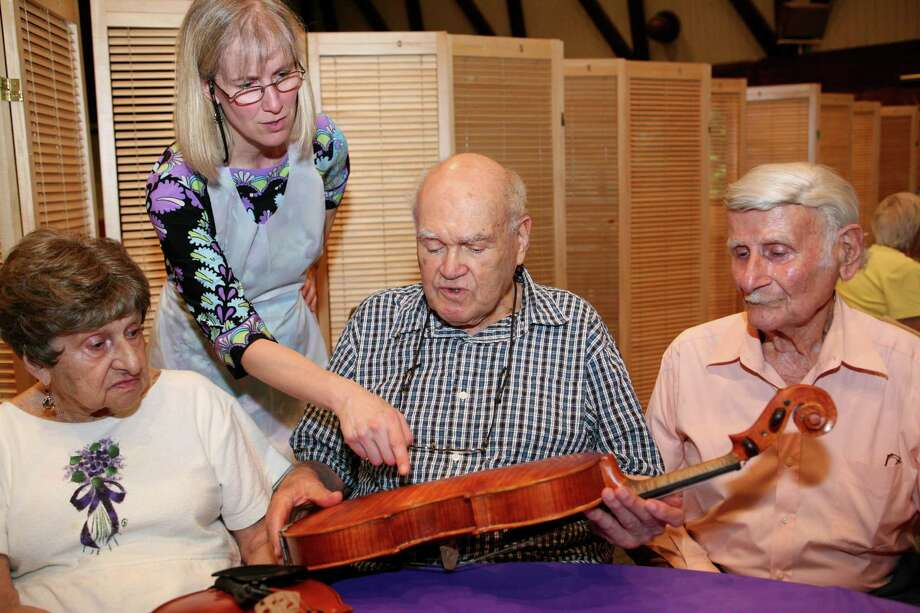 Greenwich resident Dr. Stanley Gross, center, talks with Sylvia Meyers, left, Cathy Clark, second from left, and Les Meyers, right, during lunch at Temple Sinai in Stamford Friday, August 10, 2012 about the construction of one of the violins Gross made at his home. Photo: David Ames / Greenwich Time