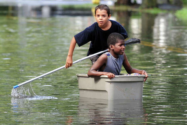 Nicolas Daniels, 9 (seated), and Joaquin Ortiz, 10, try to navigate the flood waters on Iranistan Ave., in Bridgeport, Conn. following Friday's storm, Aug. 10th, 2012. Photo: Ned Gerard / Connecticut Post