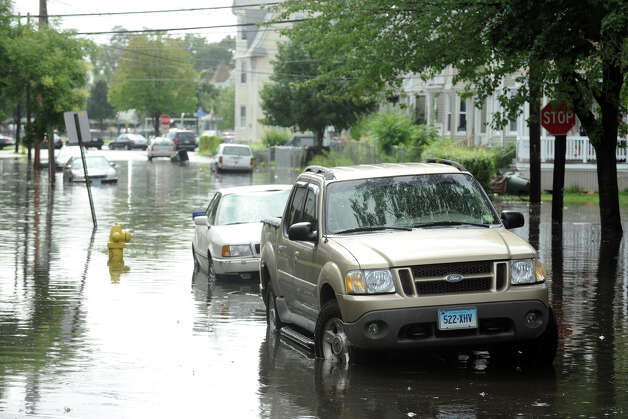 The scene along flooded Cottage Street., in Bridgeport, Conn. following Friday's storm, Aug. 10th, 2012. Photo: Ned Gerard / Connecticut Post