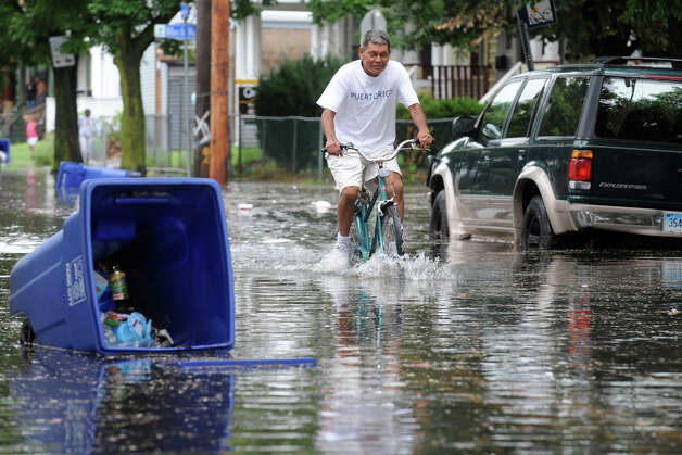 Luis Zamot rides his bike down flooded  Iranistan Ave., in Bridgeport, Conn. following Friday's storm, Aug. 10th, 2012. Photo: Ned Gerard / Connecticut Post