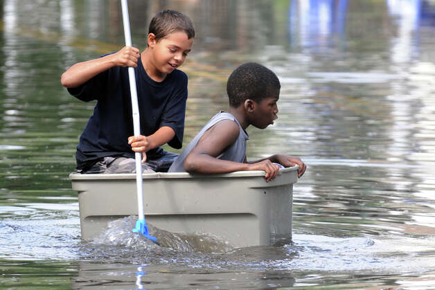 Joaquin Ortiz, 10, (left) and Nicolas Daniels, 9, try to navigate the flood waters on Iranistan Ave., in Bridgeport, Conn. following Friday's storm, Aug. 10th, 2012. Photo: Ned Gerard / Connecticut Post
