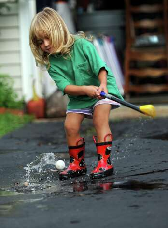 Two-year-old Sadie Sharkey hits golf balls out of the puddles in her driveway in Ansonia, Conn. Friday, August 10, 2012 following a rain storm. Photo: Autumn Driscoll / Connecticut Post