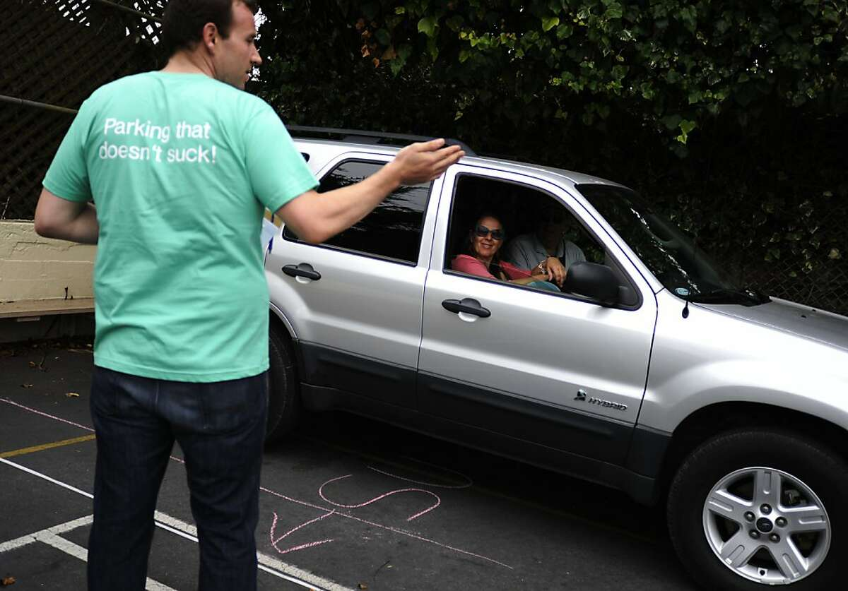 Andy Huson, left, directs Chris Davidson, center, and Joe Fahy, right, to park at their reserved parking spot at St Thomas Apostle School on Friday, Aug 10, 2012 in San Francisco, Calif.