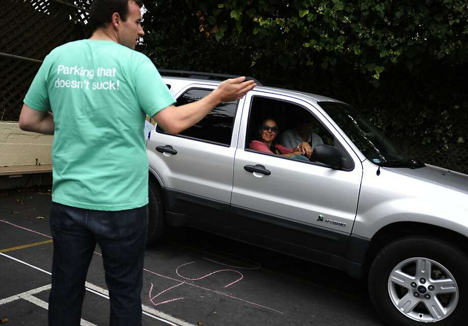 Andy Huson, left, directs Chris Davidson, center, and Joe Fahy, right, to park at their reserved parking spot at St Thomas Apostle School on Friday, Aug 10, 2012 in San Francisco, Calif. Photo: Yue Wu, The Chronicle