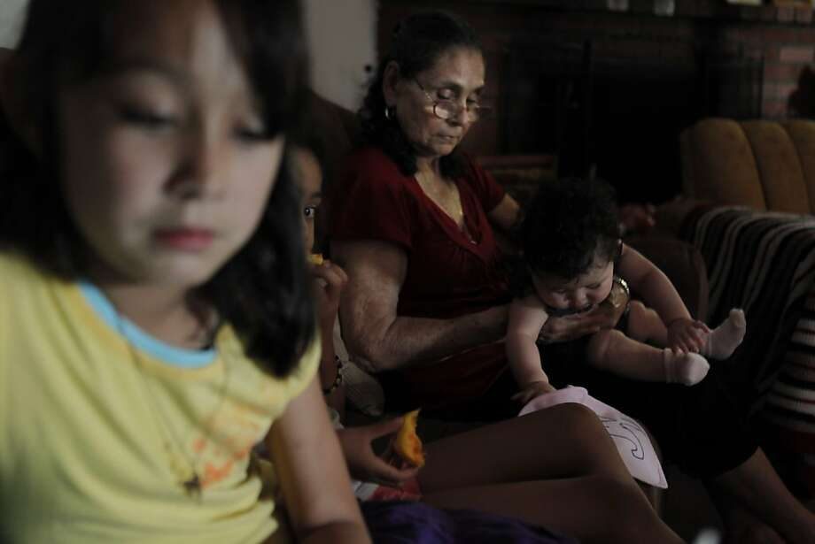 Emilia Villanueva (rear) holds granddaughter Felisa Pacheco as Felisa's sisters, Melina (left) and Isabella, play on their couch. Monthly payments on the variable-rate mortgage on the family's Castro Valley home have soared from $2,800 to $4,800. Photo: Carlos Avila Gonzalez, The Chronicle