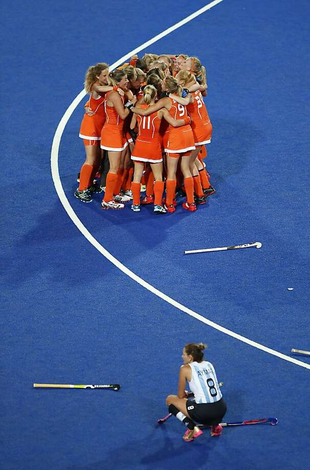 Argentina's Luciana-Aymar, bottom, looks on as Netherlands hockey players celebrate their win in a women's hockey gold medal match at the 2012 Summer Olympics, London, Friday, Aug. 10, 2012. (AP Photo/Jae C. Hong) Photo: Jae C. Hong, Associated Press