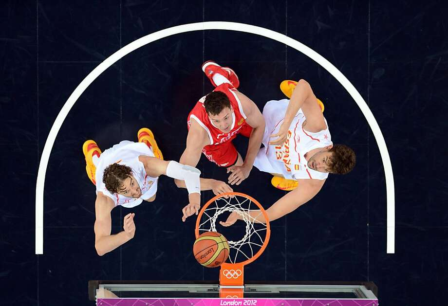 """TOPSHOTS Spanish centre Marc Gasol and Spanish forward Pau Gasol challenge Russian centre Alexander """"Sasha"""" Kaun (C) during the London 2012 Olympic Games men's semifinal basketball game bewteen Russia and Spain at the North Greenwich Arena in London on August 10, 2012. AFP PHOTO /MARK RALSTONMARK RALSTON/AFP/GettyImages Photo: Mark Ralston, AFP/Getty Images"""