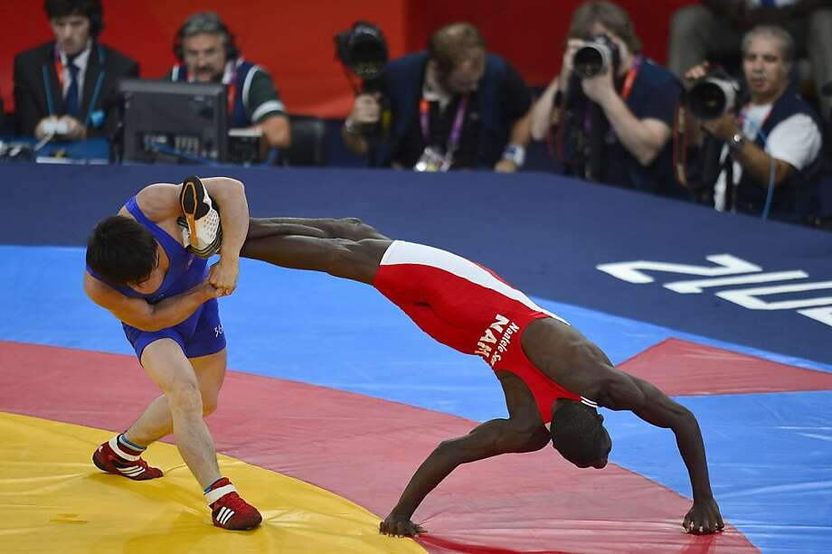 TOPSHOTS Namibia's Naatele Sem Shilimela (R) is blocked by North Korea's Yang Kyong Il during their Men's 55kg Freestyle repechage round 2 match on August 10, 2012 during the wrestling event of the London 2012 Olympic Games.  AFP PHOTO / YURI CORTEZYURI CORTEZ/AFP/GettyImages Photo: Yuri Cortez, AFP/Getty Images