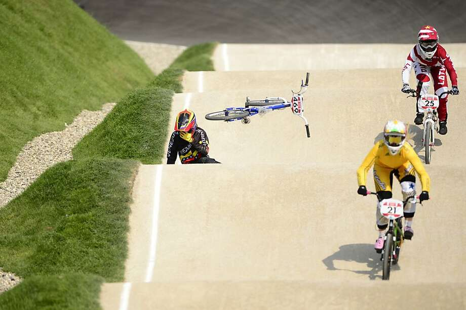 TOPSHOTS Venezuela's Stefany Hernandez (L) comes off her bike as Australia's Lauren Reynolds (C) and Latvia's Sandra Aleksejeva (R) ride by during the BMX cycling women's semi-finals event at the London 2012 Olympic Games in the Olympic Park in east London on August 10, 2012.   AFP PHOTO / LEON NEALLEON NEAL/AFP/GettyImages Photo: Leon Neal, AFP/Getty Images
