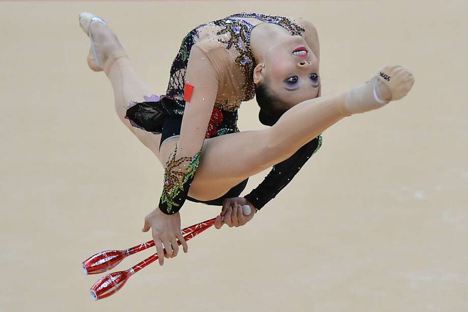 TOPSHOTS China's Deng Senyue performs her clubs program during the individual all-around qualifications of the rythmic gymnastics event of the London Olympic Games on August 10, 2012 at Wembley arena in London. AFP PHOTO / BEN STANSALLBEN STANSALL/AFP/GettyImages Photo: Ben Stansall, AFP/Getty Images