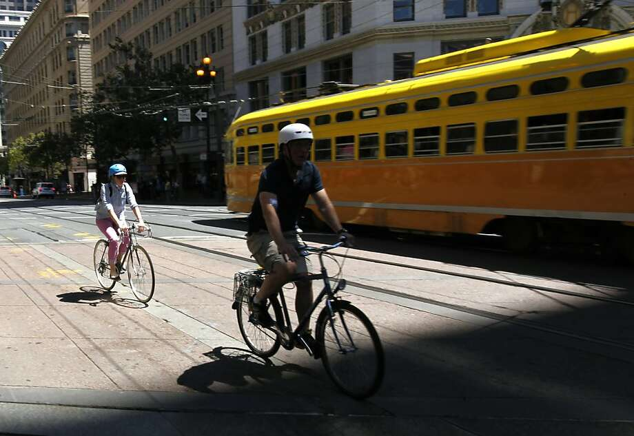 "Cyclists ride on Market Street. ""Cycle tracks,"" higher than the street but lower than the sidewalk, are being considered. Photo: Paul Chinn, The Chronicle"