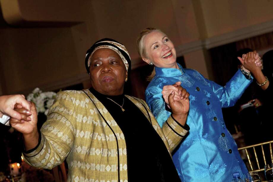 FILE - In this Aug. 7, 2012 file photo, Secretary of State Hillary Rodham Clinton holds hands during a dance with other officials including African Union Chair-Designate Nkosazana Dlamini-Zuma, during a gala dinner at Sefako M. Makgatho Presidential Guest House in Pretoria, South Africa. On an epic safari through Africa, U.S. Secretary of State Hillary Rodham Clinton braved Uganda's Ebola outbreak, dealt with a swarm of angry Malawian bees, endured a rare South African snowstorm and shimmied on a dance floor in South Africa, earning the nickname the Secretary of Shake. And as she wrapped up her nine-nation African tour on Friday in Benin,Clinton shattered her own already herculean travel record.  (AP Photo/Jacquelyn Martin, File, Pool) Photo: Jacquelyn Martin, Associated Press / AP POOL