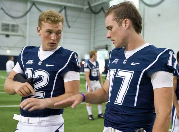 Connecticut quarterback Casey Cochran, left, takes a brace off to show his injury to fellow quarterback Blaise Driscoll, right, during an NCAA football media day in Storrs, Conn., Friday, Aug. 10, 2012.  (AP Photo/Jessica Hill) Photo: Jessica Hill, Associated Press / FR125654 AP