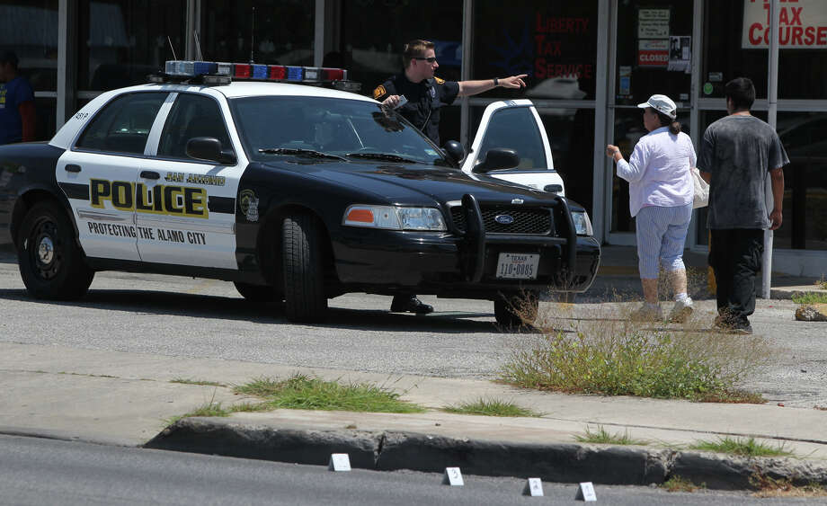 A San Antonio police officer directs pedestrians away from a crime scene Friday August 10, 2012 on the 2900 block of West avenue. Police said a man walking down West avenue and was shot in the arm there and was transported by E.M.S. to University Hospital with a non-life threatening injury. Police said they were looking for a yellow Hummer that was seen in the area. Photo: John Davenport/Express-News