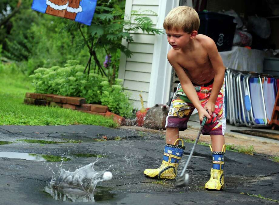 Five-year-old Eddie Sharkey hits golf balls out of the puddles in his driveway in Ansonia, Conn. Friday, August 10, 2012 following a rain storm. Photo: Autumn Driscoll / Connecticut Post
