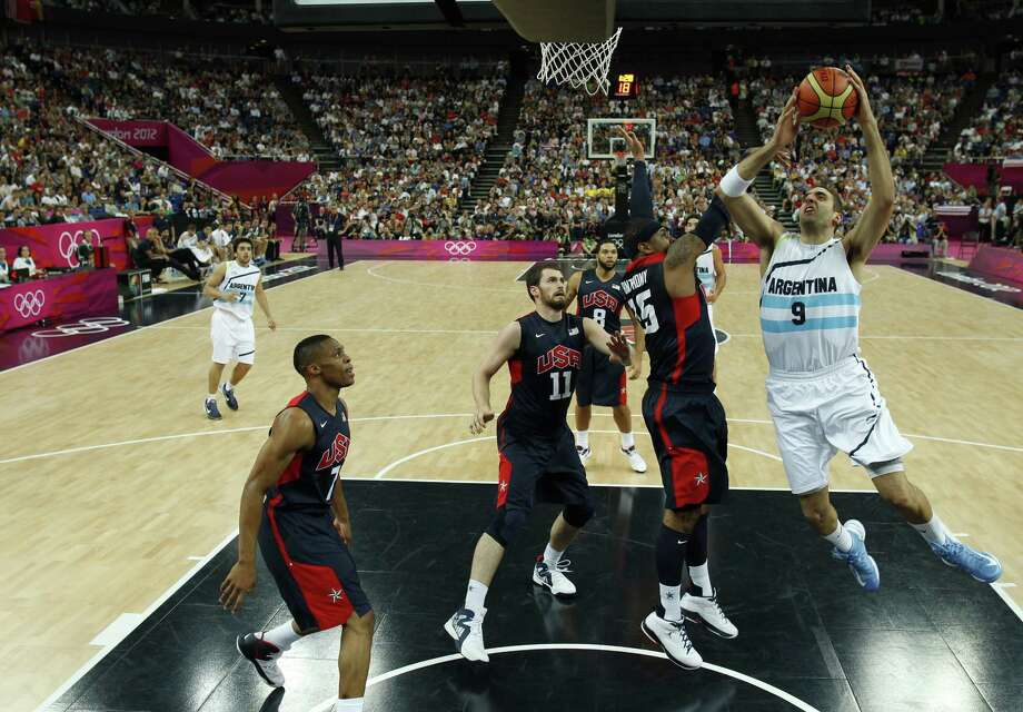 LONDON, ENGLAND - AUGUST 10: Juan Gutierrez (R) of Argentina shoots over Carmelo Anthony (2nd R) of the United States during the Men's Basketball semi-final match between Argentina and the USA on Day 14 of the London 2012 Olympic Games at North Greenwich Arena on August 10, 2012 in London, England. Photo: Pool, Getty Images / 2012 Getty Images