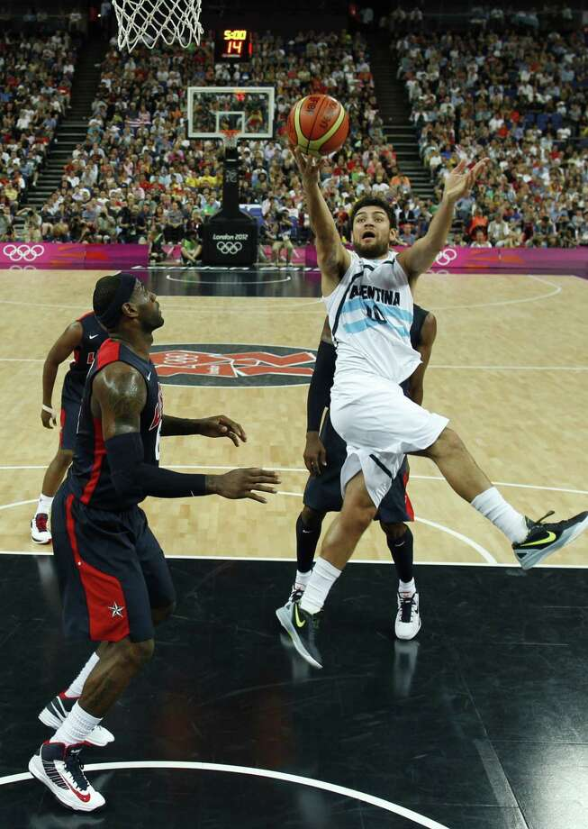 Argentina's Carlos Delfino (R) throws up a shot against the US during the London 2012 Olympic Games men's semifinal basketball game between Argentina and the USA at the North Greenwich Arena in London on August 10, 2012. AFP PHOTO/ POOL/SERGIO PEREZSERGIO PEREZ/AFP/GettyImages Photo: SERGIO PEREZ, AFP/Getty Images / AFP