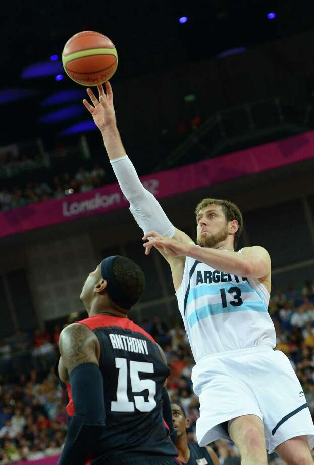 Argentinian forward Andres Nocioni (R) jumps for the ball over US forward Carmelo Anthony during the London 2012 Olympic Games men's semifinal basketball game between Argentina and the USA at the North Greenwich Arena in London on August 10, 2012. AFP PHOTO /MARK RALSTONMARK RALSTON/AFP/GettyImages Photo: MARK RALSTON, AFP/Getty Images / AFP