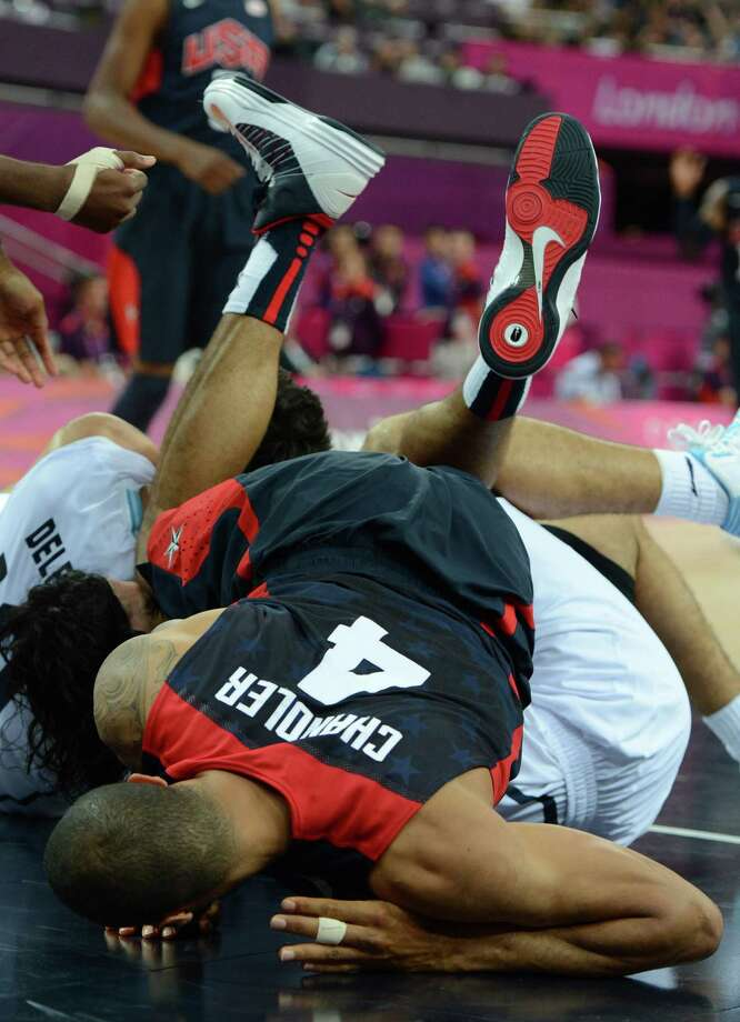 US centre Tyson Chandler falls to the ground as he vies with Argentinian forward Luis Scola during the London 2012 Olympic Games men's semifinal basketball game between Argentina and the USA at the North Greenwich Arena in London on August 10, 2012. AFP PHOTO /MARK RALSTONMARK RALSTON/AFP/GettyImages Photo: MARK RALSTON, AFP/Getty Images / AFP