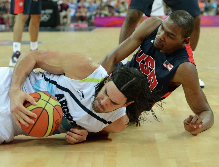 Argentinian forward Luis Scola (L) falls to the ground as he vies with US forward Kevin Durant during the London 2012 Olympic Games men's semifinal basketball game between Argentina and the USA at the North Greenwich Arena in London on August 10, 2012. AFP PHOTO /MARK RALSTONMARK RALSTON/AFP/GettyImages Photo: MARK RALSTON, AFP/Getty Images / AFP