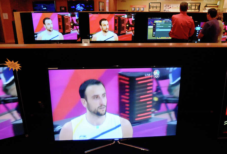Manu Ginobili flashes on the screens at Bjorn's audio and video store as customers are shown televisions buy employees on Friday, August 10, 2012. The Olympic basketball showdown between Argentina and the U.S.A. was shown on the screens throughout the store. Photo: Kin Man Hui, SAN ANTONIO EXPRESS-NEWS / ©2012 San Antonio Express-News