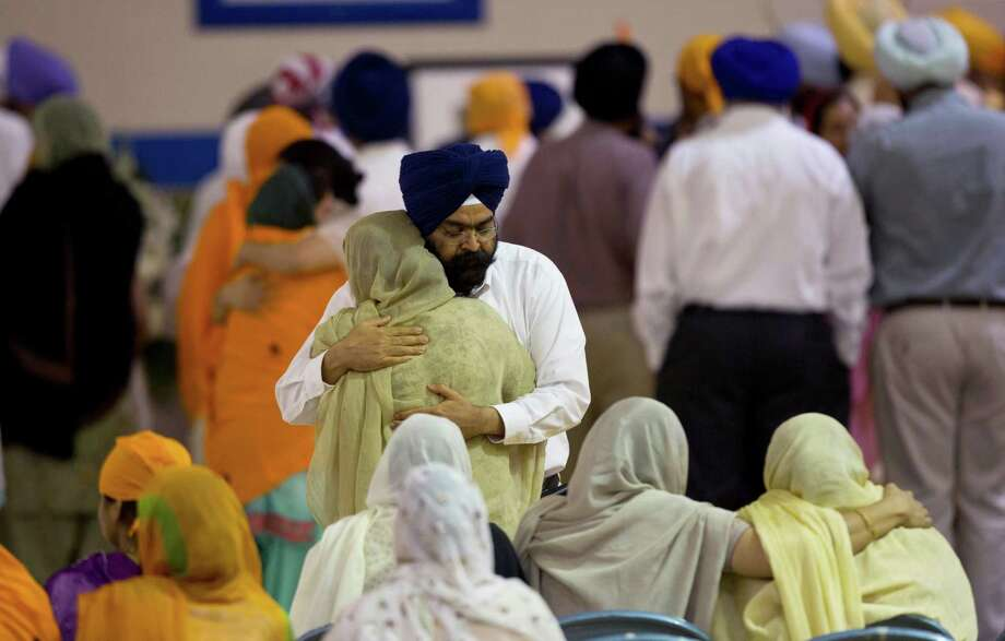 Mourners provide comfort at the funeral and memorial service for the six victims of the Sikh temple of Wisconsin mass shooting in Oak Creek, Wis., Friday, Aug 10, 2012. The public service was held in the Oak Creek High School. Three other people were wounded in the shooting last Sunday at the temple.   Wade Michael Page, 40, killed five men and one woman, and injured two other men. Authorities say Page then ambushed the first police officer who responded, shooting him nine times and leaving him in critical condition. A second officer then shot Page in the stomach, and Page took his own life with a shot to the head. (AP Photo/Jeffrey Phelps) Photo: JEFFREY PHELPS