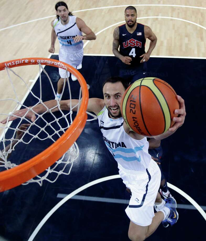 LONDON, ENGLAND - AUGUST 10:  Manu Ginobili of  Argentina scores as teammate  Luis Scola, left, and Tyson Chandler, right, of the United States look on during the Men's Basketball semi-final match between Argentina and the USA on Day 14 of the London 2012 Olympic Games at North Greenwich Arena on August 10, 2012 in London, England. Photo: Pool, Getty Images / 2012 Getty Images