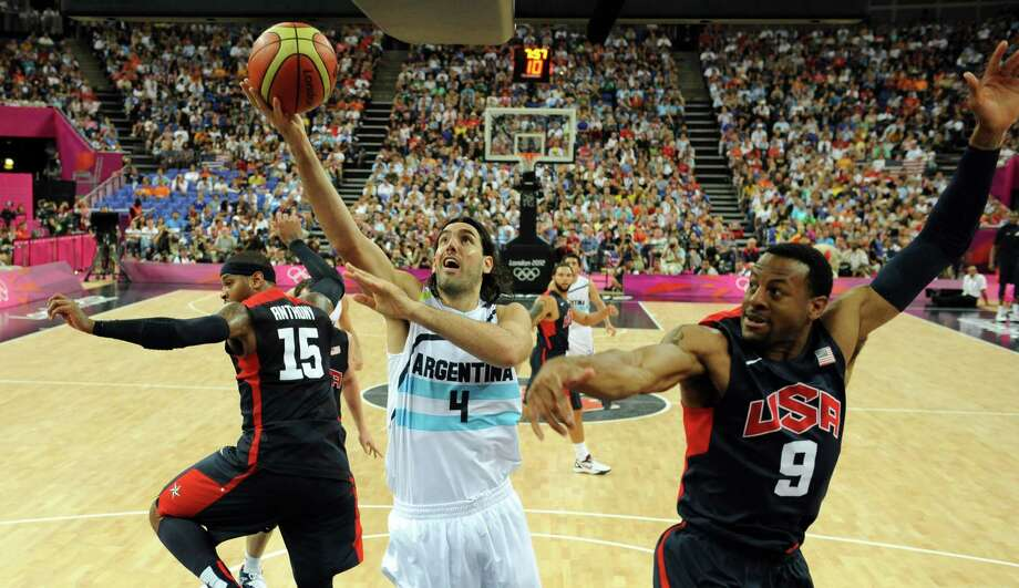 LONDON, ENGLAND - AUGUST 10:  Andre Iguodala (R) and Carmelo Anthony (L) of the United States challenge Luis Scola of Argentina during the Men's Basketball semi-final match between Argentina and the USA on Day 14 of the London 2012 Olympic Games at North Greenwich Arena on August 10, 2012 in London, England. Photo: Pool, Getty Images / 2012 Getty Images