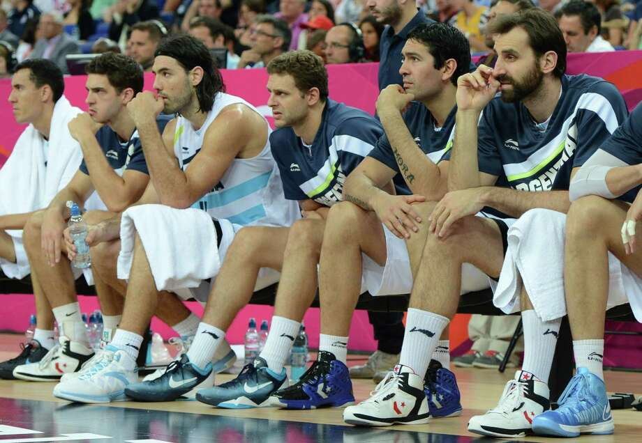Argentinian players sit on the sidelines during the London 2012 Olympic Games men's semifinal basketball game between Argentina and the USA at the North Greenwich Arena in London on August 10, 2012. AFP PHOTO /MARK RALSTONMARK RALSTON/AFP/GettyImages Photo: MARK RALSTON, AFP/Getty Images / AFP