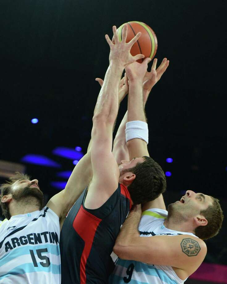 Argentinian forward Federico Kammerichs (L) and Argentinian centre Juan Pedro Gutierrez (R)  jump for the ball with US forward Kevin Love during the London 2012 Olympic Games men's semifinal basketball game between Argentina and the USA at the North Greenwich Arena in London on August 10, 2012. AFP PHOTO /MARK RALSTONMARK RALSTON/AFP/GettyImages Photo: MARK RALSTON, AFP/Getty Images / AFP