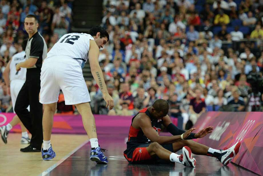 Argentinian centre Martin Leiva (L) helps US guard Chris Paul (R) off the ground during the London 2012 Olympic Games men's semifinal basketball game between Argentina and the USA at the North Greenwich Arena in London on August 10, 2012. AFP PHOTO /TIMOTHY A.  CLARYTIMOTHY A. CLARY/AFP/GettyImages Photo: TIMOTHY A. CLARY, AFP/Getty Images / AFP