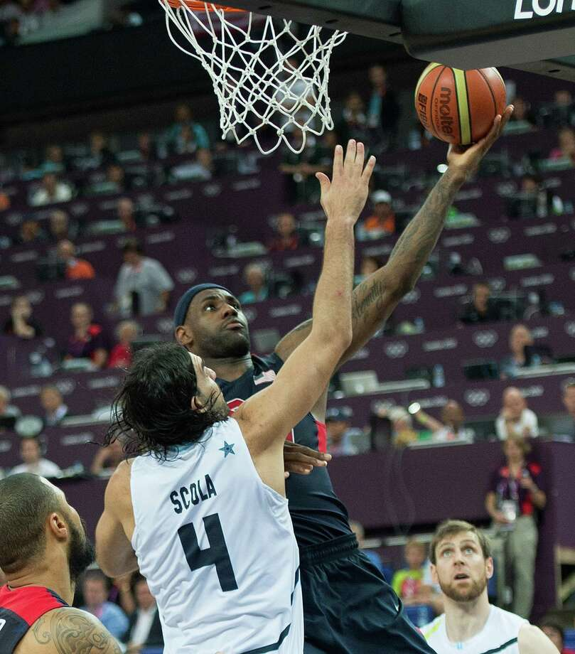 USA's Lebron James (6) scores on Argentina's Luis Scola (4) during their semifinals game at the Basketball Arena at the North Greenwich Arena during the 2012 Summer Olympic Games in London, England, Thursday, August 9, 2012. USA defeated Argentina 109-83 to advance to the Gold Medal game. (Harry E. Walker/MCT) Photo: Harry E. Walker, McClatchy-Tribune News Service / Harry E. Walker, Copyright 2012