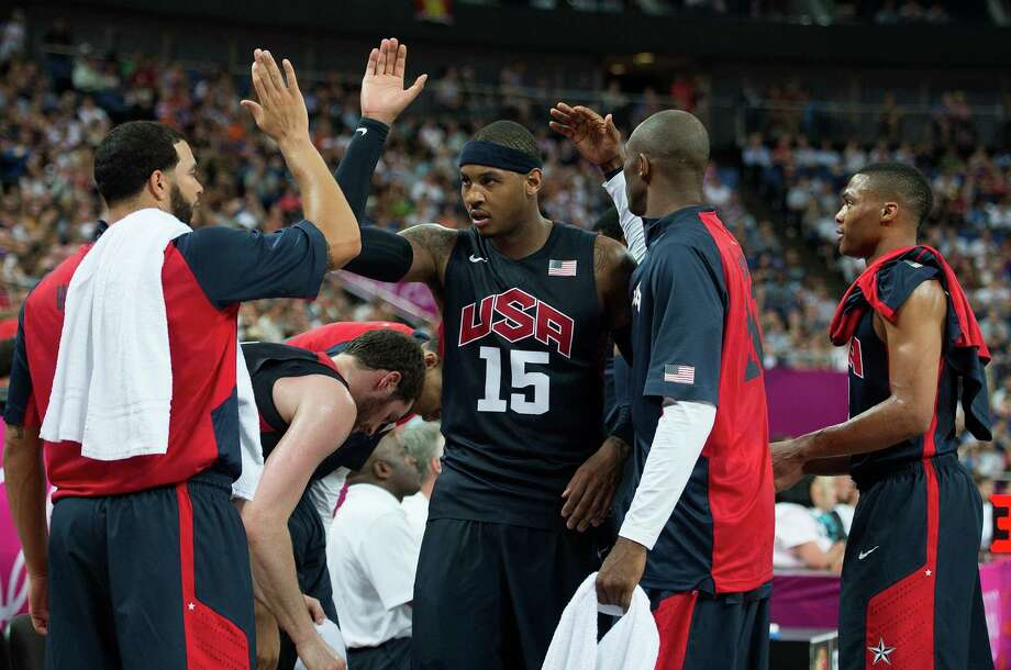 USA's Carmelo Anthony (15) is greet by teammates as he comes to the bench after hitting a series of three-point shots against Argentina during their semifinals game at the Basketball Arena at the North Greenwich Arena during the 2012 Summer Olympic Games in London, England, Thursday, August 9, 2012. USA defeated Argentina 109-83 to advance to the Gold Medal game. (Harry E. Walker/MCT) Photo: Harry E. Walker, McClatchy-Tribune News Service / Harry E. Walker, Copyright 2012