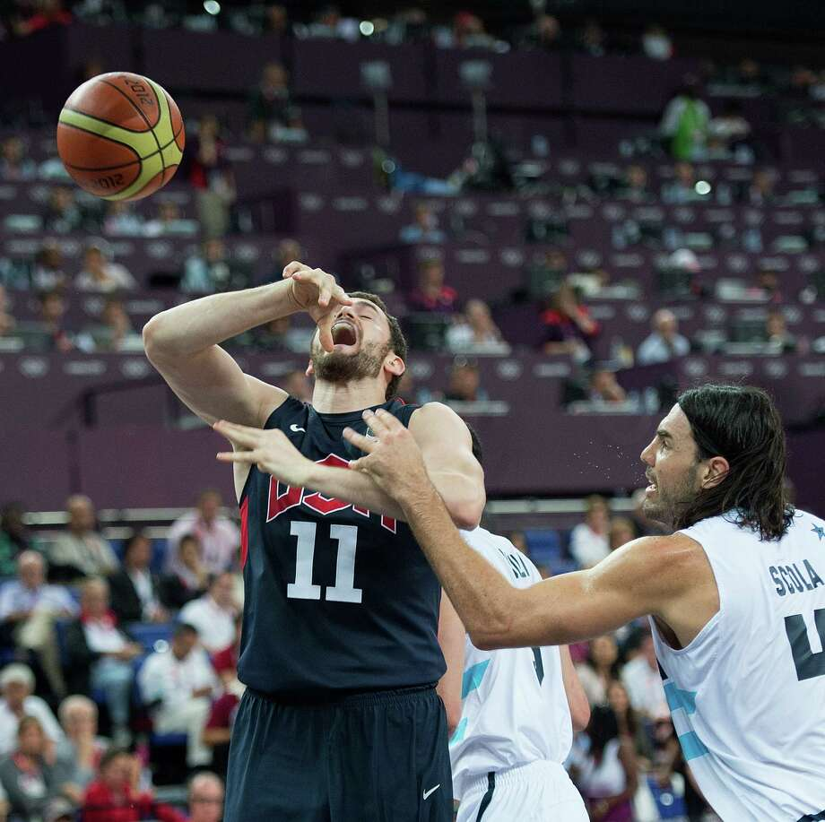 USA's Kevin Love (11) looses the ball as he is fouled by Argentina's Luis Scola (4) during their semifinals game at the Basketball Arena at the North Greenwich Arena during the 2012 Summer Olympic Games in London, England, Thursday, August 9, 2012. USA defeated Argentina 109-83 to advance to the Gold Medal game. (Harry E. Walker/MCT) Photo: Harry E. Walker, McClatchy-Tribune News Service / Harry E. Walker, Copyright 2012