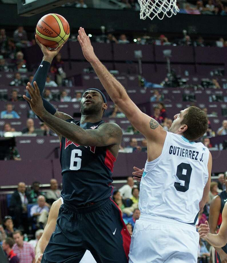 USA's Lebron James (6) scores over Argentina's Juan Gutierrez (9) during their semifinals game at the Basketball Arena at the North Greenwich Arena during the 2012 Summer Olympic Games in London, England, Thursday, August 9, 2012. USA defeated Argentina 109-83 to advance to the Gold Medal game. (Harry E. Walker/MCT) Photo: Harry E. Walker, McClatchy-Tribune News Service / Harry E. Walker, Copyright 2012
