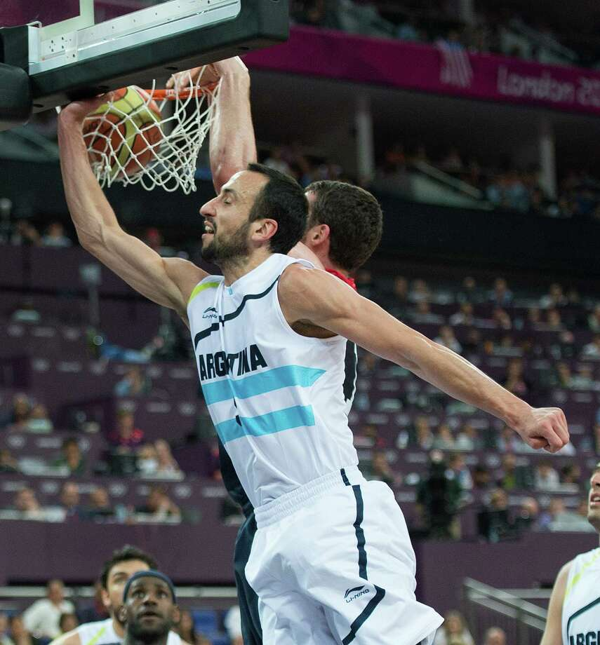 USA's Kevin Love (11) slam dunks on Argentina's Manu Ginobili (5) during their semifinals game at the Basketball Arena at the North Greenwich Arena during the 2012 Summer Olympic Games in London, England, Thursday, August 9, 2012. USA defeated Argentina 109-83 to advance to the Gold Medal game. (Harry E. Walker/MCT) Photo: Harry E. Walker, McClatchy-Tribune News Service / Harry E. Walker, Copyright 2012