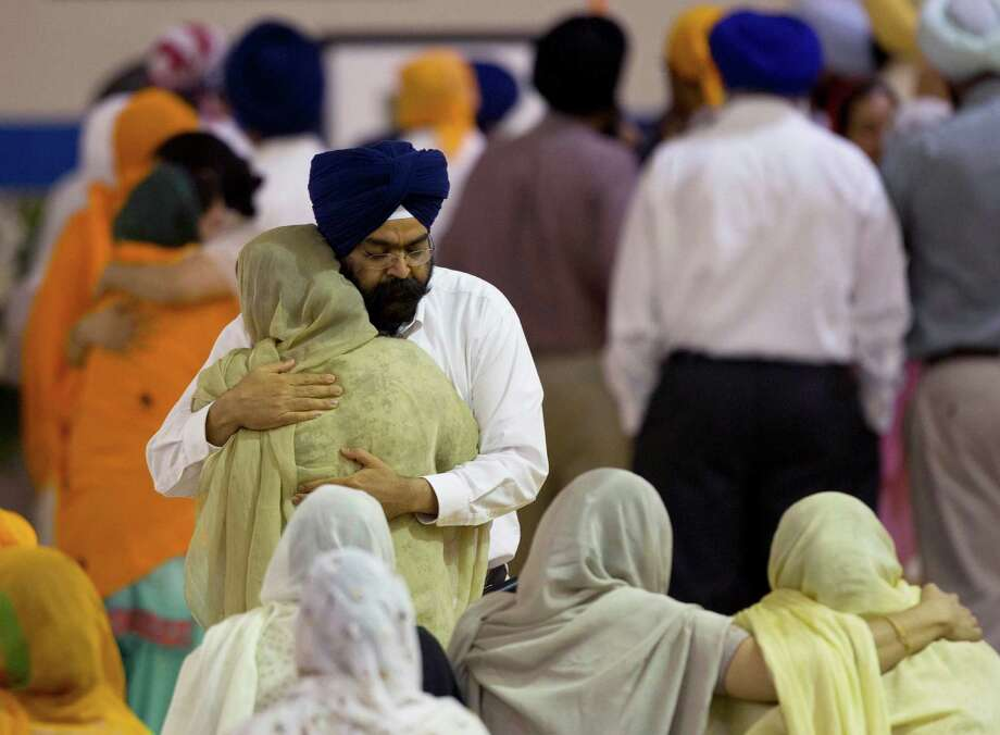 Mourners provide comfort Friday, Aug. 10, 2012 at the funeral and memorial service held in the Oak Creek High School for the six victims of Sunday's mass shooting at the Sikh Temple of Wisconsin in Oak Creek, Wis. Wade Michael Page, 40, killed five men and one woman, and injured two other men. Authorities say Page then ambushed the first police officer who responded, shooting him nine times and leaving him in critical condition. A second officer then shot Page in the stomach, and Page took his own life with a shot to the head. (AP Photo/Jeffrey Phelps) Photo: Jeffrey Phelps / FR59249 AP