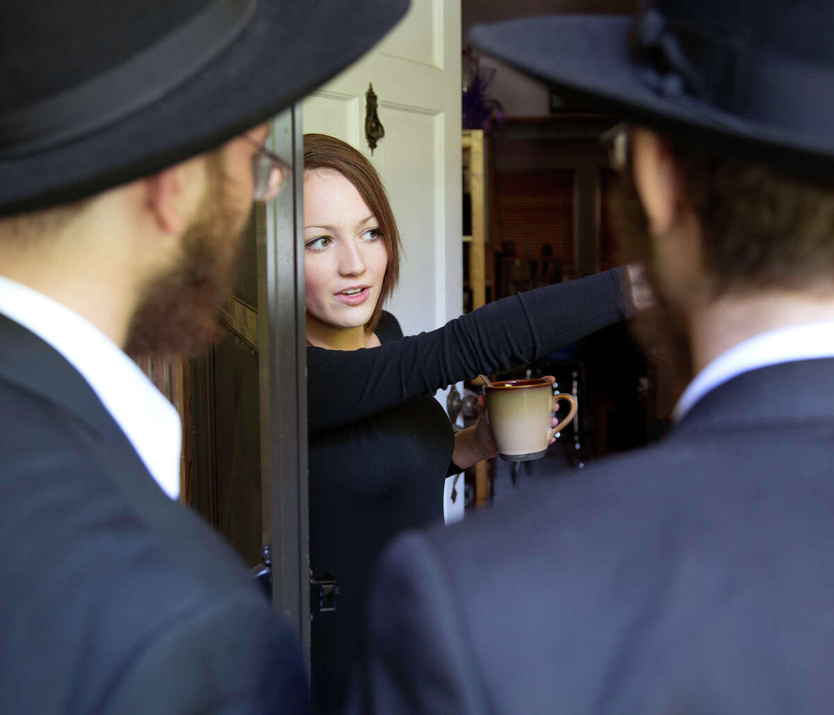 Isabelle Forman greets Kopel Silberberg, left, and Eli Block, right, as they visit the Forman home to inspect and replace the mezuzahs that traditionally hangs at the entrance of Jewish homes, Wednesday, August 8, 2012.