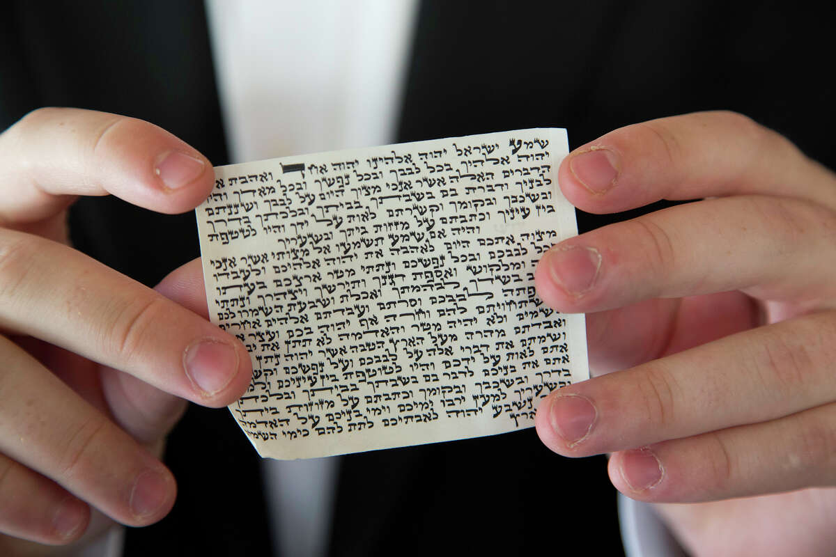 Kopel Silberberg shows the hand-lettered Hebrew verses from the Torah which rests inside the mezuzah that traditionally hangs at the entrance of Jewish homes, Wednesday, August 8, 2012.