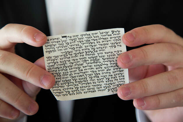Kopel Silberberg shows the hand-lettered Hebrew verses from the Torah which rests inside the mezuzah that traditionally hangs at the entrance of Jewish homes, Wednesday, August 8, 2012. Photo: J. MICHAEL SHORT, FOR THE EXPRESS-NEWS / Photo Copyright 2012 by J. Michael Short