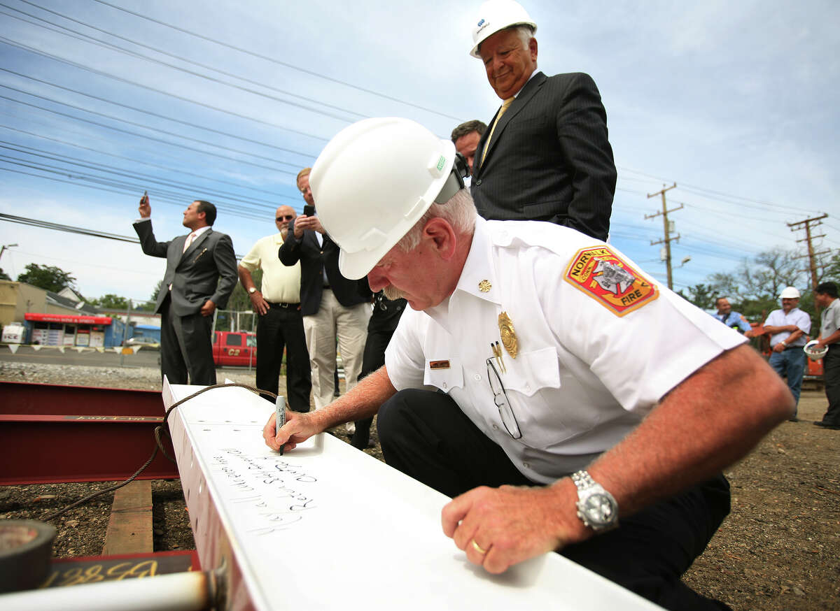 As Mayor Richard Moccia looks on, Fire Chief Denis McCarthy signs the ceremonial final beam on the new Norwalk Central Fire Station at 121 Connecticut Avenue in Norwalk on Tuesday, August 7, 2012.