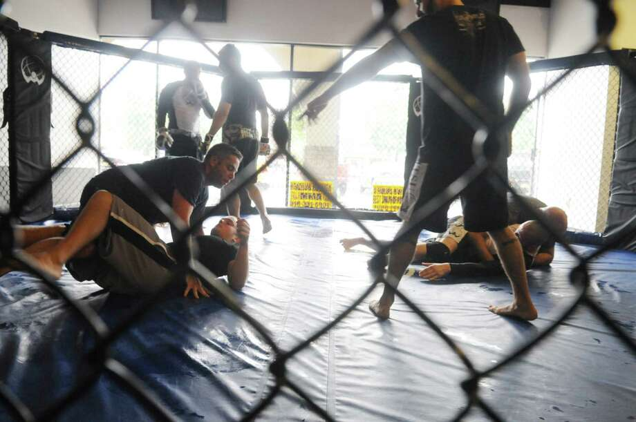 Fighters work with instructors during a training session Friday Aug. 10, 2012, at Atlas Jiu Jitsu in Colonie, N.Y., where  Assembly candidate Tim Nichols announced that he would allow Mixed Martial Arts in the state. Nichols is the former chief of staff for Bob Reilly who was noted for his oppositions to allowing MMA events in New York. (Will Waldron / Times Union) Photo: Will Waldron