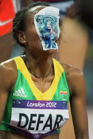 Ethiopia's Meseret Defar covers her face with a religious picture she carried in her top during the race as she celebrates after winning the women's 1500-meter finalat the 2012 London Olympics on Friday, Aug. 10, 2012. Photo: Smiley N. Pool, Houston Chronicle / © 2012  Houston Chronicle