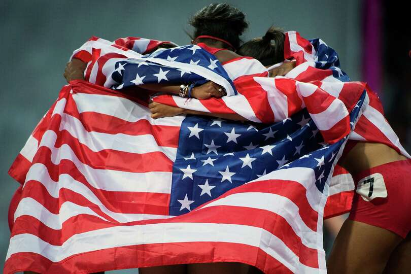 The USA relay team of Carmelita Jeter, Tianna Madison, Allyson Felix, and Bianca Knight embrace unde