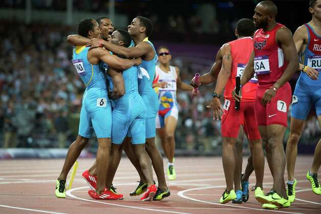 The men's 4x400-meter relay team from the Bahamas of, from left, Chris Brown, Demetrius Pinder, Michael Mathieu and Ramon Miller celebrates after winning the gold medal in the race as USA's Angelo Taylor looks on at the 2012 London Olympics on Friday, Aug. 10, 2012. Pinder, from Texas A&M, ran the second leg for the Bahamas in the victory. Photo: Smiley N. Pool, Houston Chronicle / © 2012  Houston Chronicle