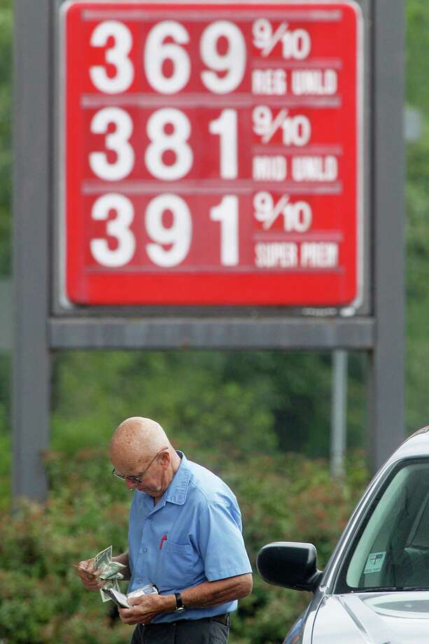 George Matkowski, of Montpelier, reaches into his wallet to pay for gas, Friday, Aug. 10, 2012, in Montpelier, Vt. A rise in the price of crude oil and problems with refineries and pipelines in the West Coast and Midwest have caused prices at the pump to surge upward. (AP Photo/Toby Talbot) Photo: Toby Talbot