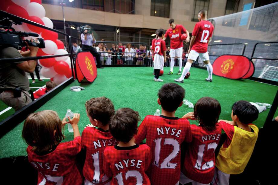 Children gather to watch Manchester United players Friday outside the New York Stock Exchange. The team's shares in an initial public offering ended flat at $14. Photo: Jin Lee / FR159730 AP