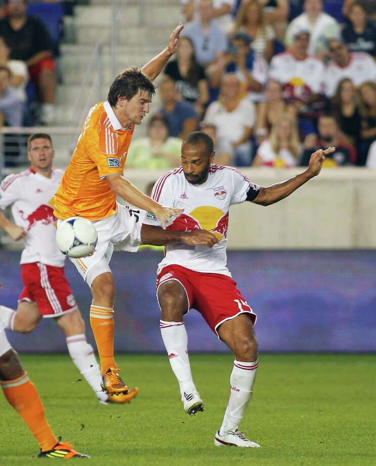 Bobby Boswell tries to keep the ball and fend off  Thierry Henry. Photo: Andy Marlin, Getty Images / 2012 Getty Images